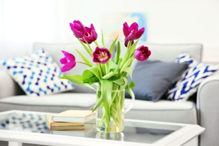 A clean living room with a bouquet of spring flowers on the coffee table