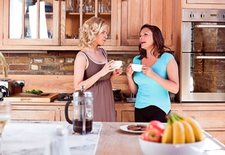 Two women drinking coffee in a kitchen