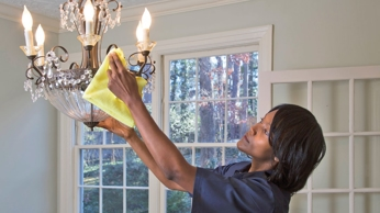 Maid Right employee dusting a chandelier