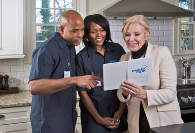 Maid Right customer and team members reviewing a brochure