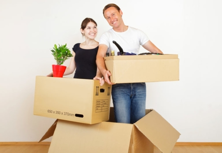 Man and woman holding moving boxes and smiling