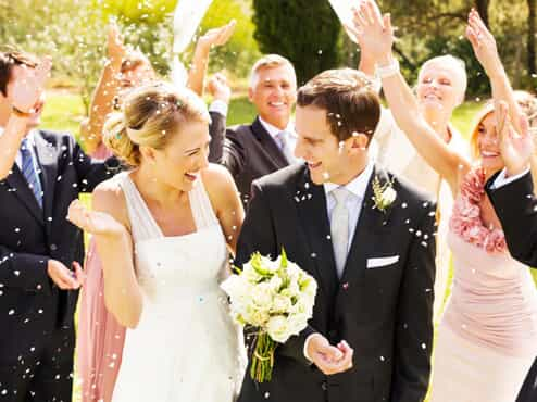 Bride and groom walking down the aisle after their wedding ceremony while guests throw confetti
