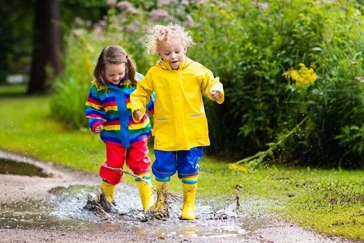 young boy and girl playing in a rain puddle