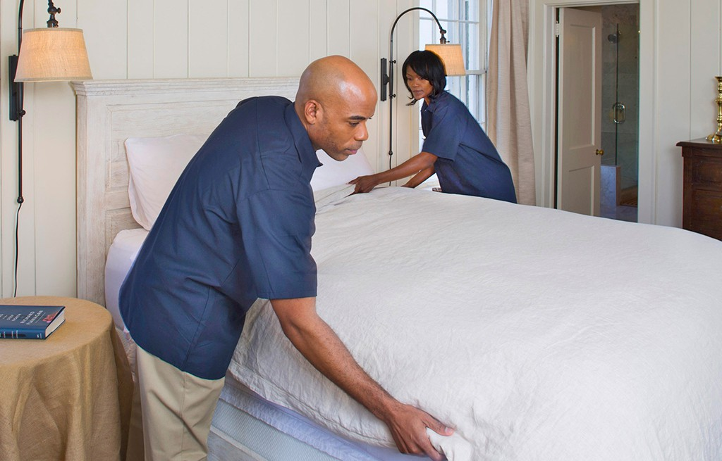 two housekeepers making a bed