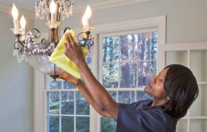 Woman wiping down lamp for maid spring cleaning services in Glendale.