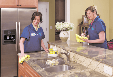 Two Maid Right team members cleaning a kitchen surface
